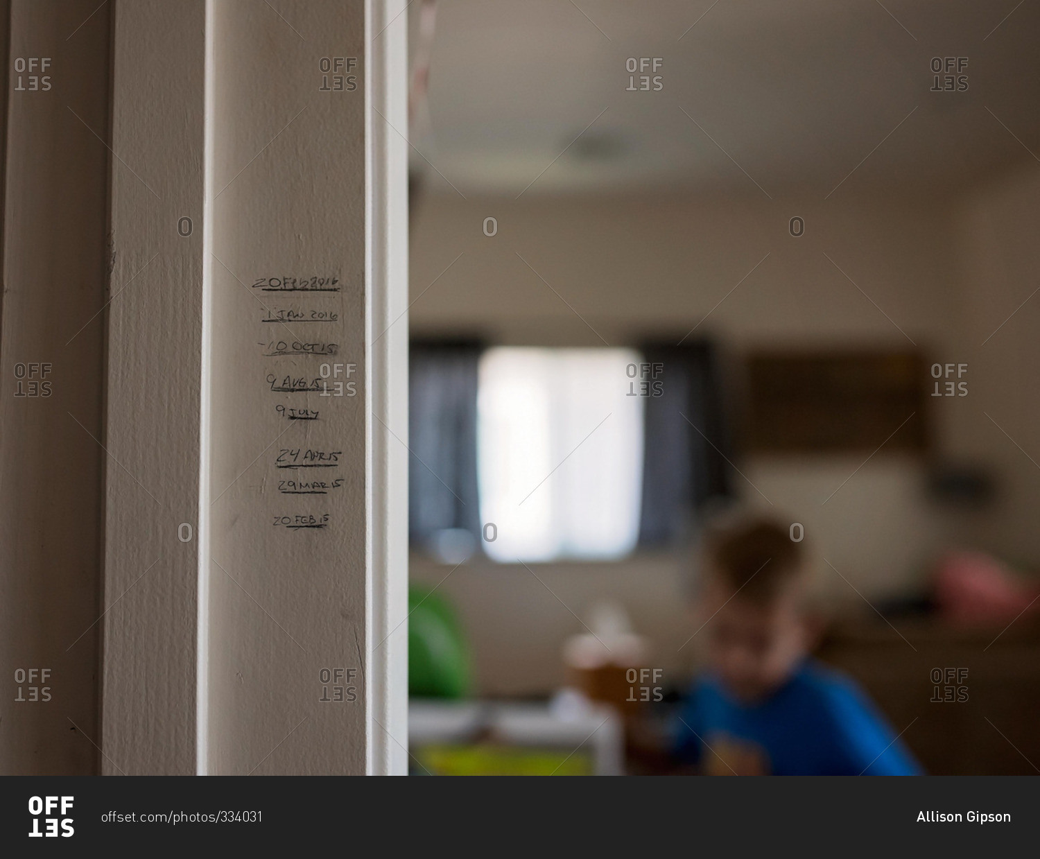 Little boy and height marks on a door frame stock photo - OFFSET