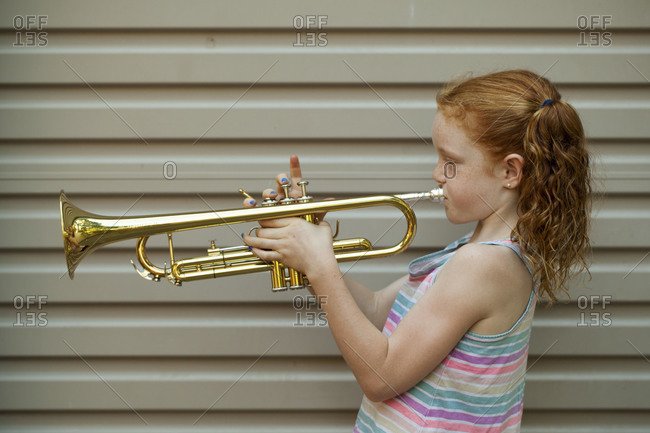 Red-haired young girl practicing trumpet