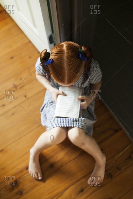 Overhead view of young girl reading book