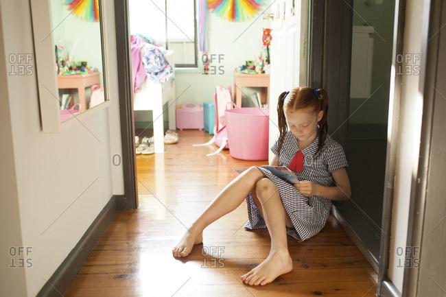 Girl reading book on floor outside bedroom