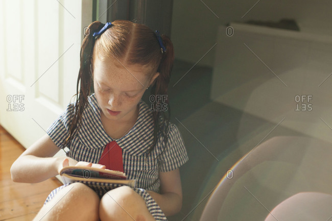Closeup of red-haired girl reading book