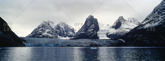 Jagged mountain peaks rise above a glacier in a arctic fjord