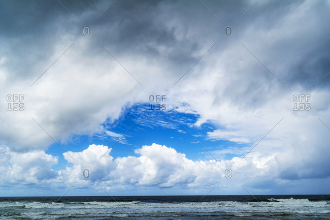 A patch of blue sky appears over an ocean during a storm