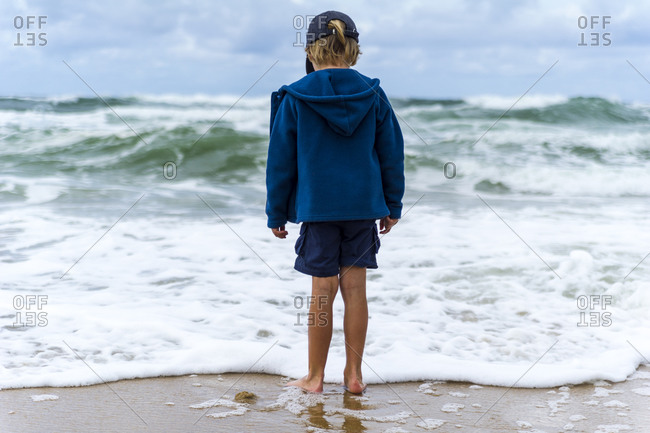 A boy playing in the shallows as storm surge waves roll onto an empty beach