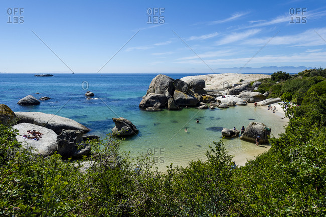Tourists swimming between boulders in the clear waters of a sheltered bay