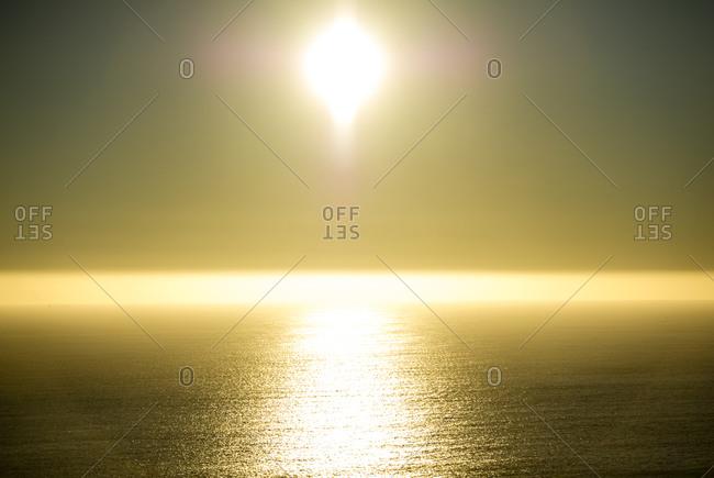 The sun casts a golden pillar on the ocean as it dips toward sunset