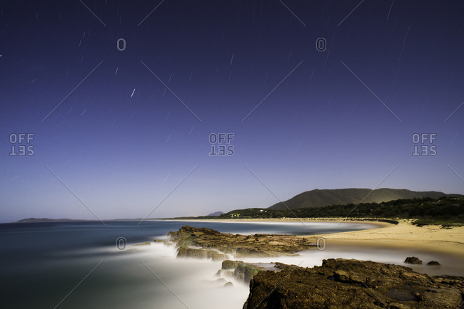 Stars streaking through a night sky on the east coast of Australia Norther brother in the background lit up by the town of Laurieton