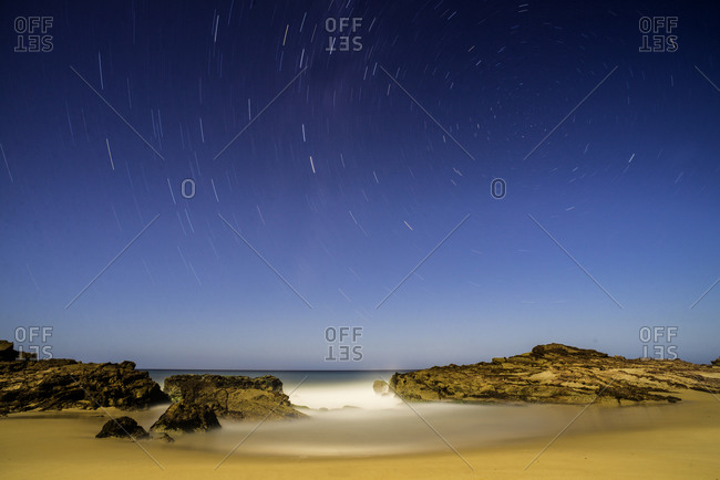 A night scene on the Australian coastline, showing movement in the stars