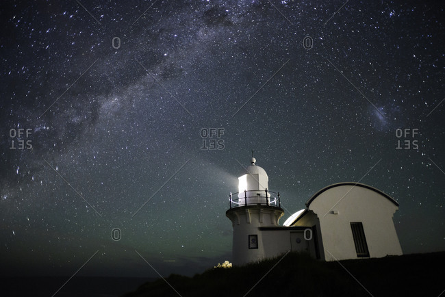 Port Macquarie lighthouse shines in the foreground with the Milky Way lighting up the night sky behind