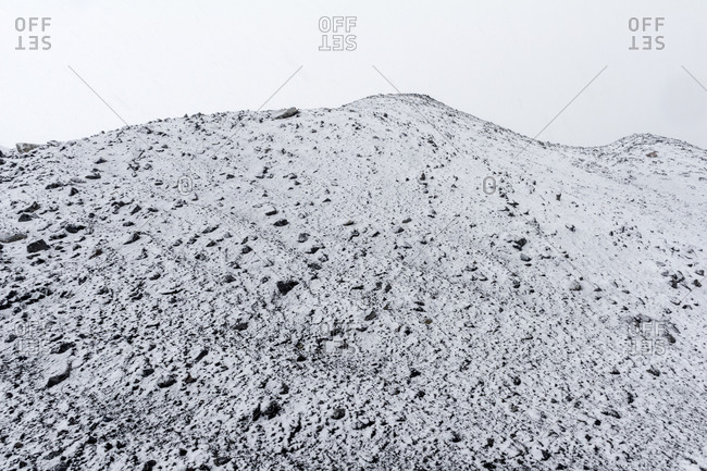 A barren volcanic slope covered in snow during a storm