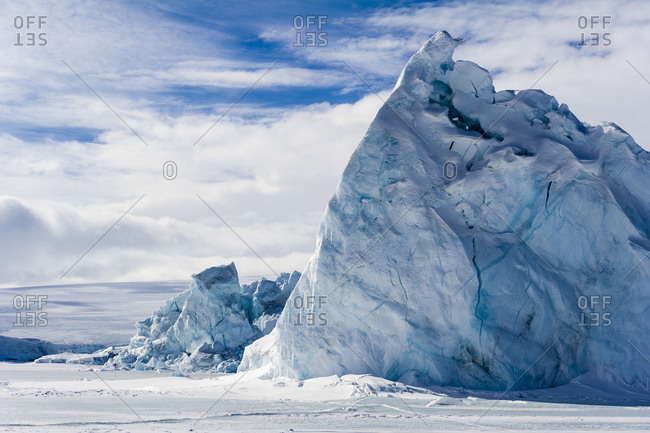 An enormous jagged iceberg trapped in frozen sea ice