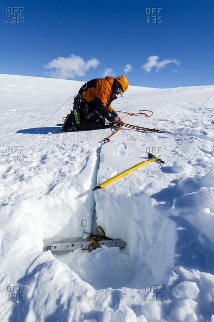 Ross Island, Antarctica - December 6, 2014: Ice guides digging snow anchors to hold ropes to enter a crevasse on the slopes of Mount Erebus in Antarctica