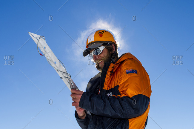Ross Island, Antarctica - December 6, 2014: Steam rises from the head of an ice guide preparing a snow anchor to enter a crevasse on the slopes of Mount Erebus in Antarctica