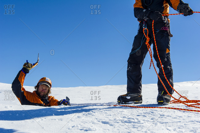 Ross Island, Antarctica - December 6, 2014: Ice guides entering a crevasse on the slopes of Mount Erebus in Antarctica