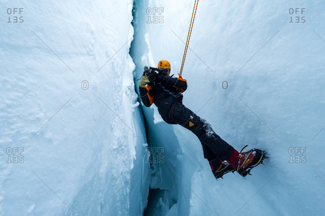 Ross Island, Antarctica - December 6, 2014: A cameraman filming from the sheer icy walls of a crevasse on the slopes of Mount Erebus in Antarctica