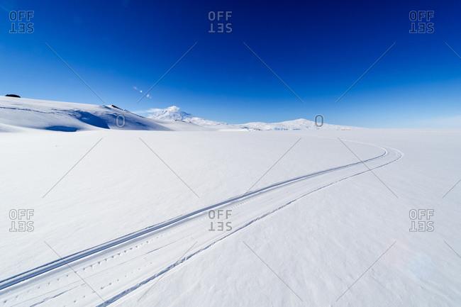 Skiddoo tracks cross the snow on the vast barren Ross Ice Shelf