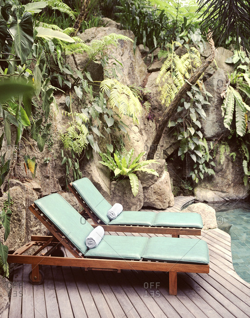 Lounge chairs at a waterfall pool at a tropical resort