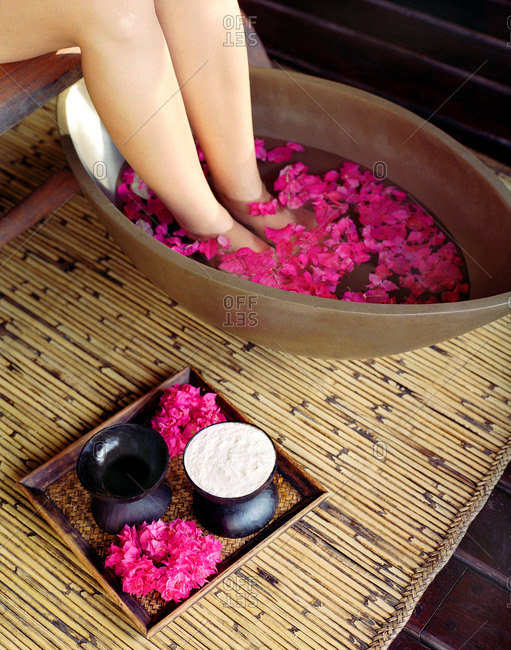 Woman soaking her feet in a bath of pink flower petals