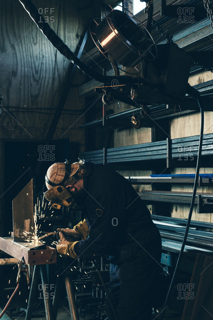 Man in workshop welding metal