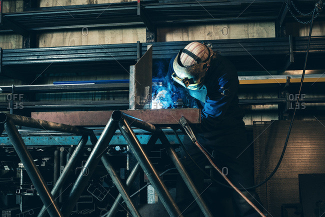 Man in a workshop welding metal
