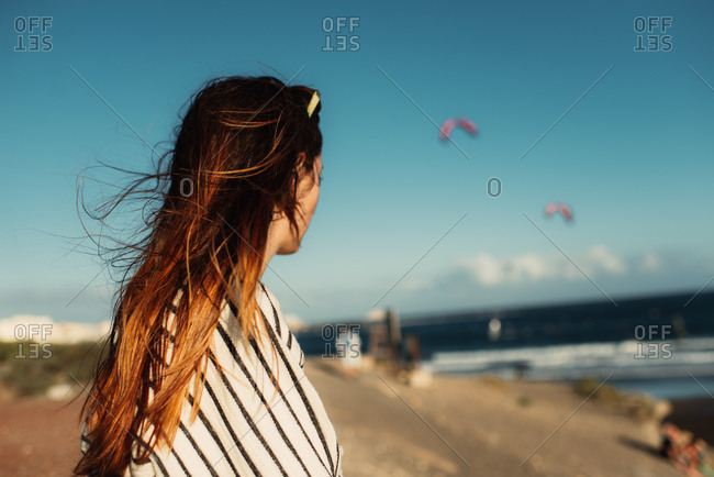 Woman looking out over the ocean from a beach in Tenerife, Spain