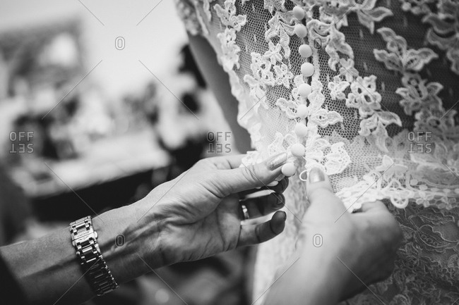Fastening buttons on bride's dress