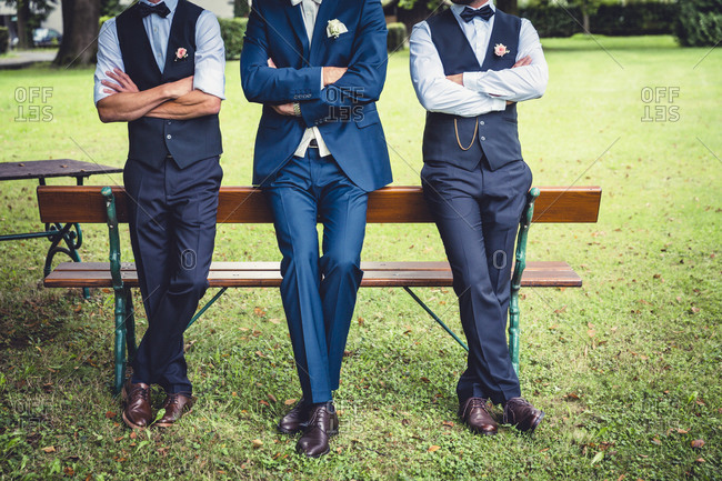 Groomsmen resting against bench