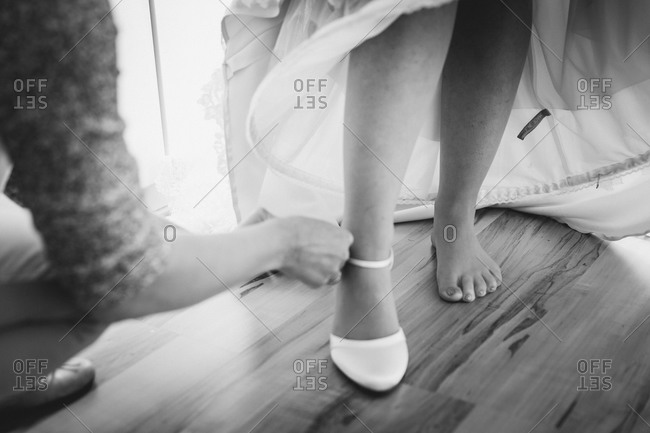 Putting on bride's shoe