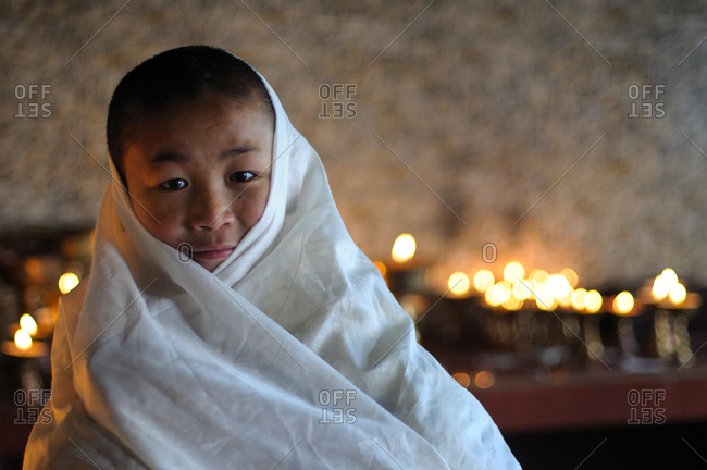 Sikkim, India - November 22, 2014: Buddhist boy wrapped in a white cloth