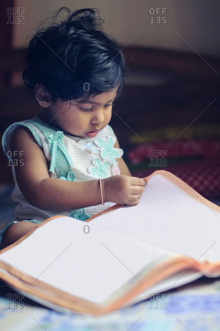 Little girl turning the pages of a blank book