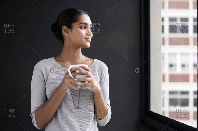 Woman holding a coffee cup and looking out her office window