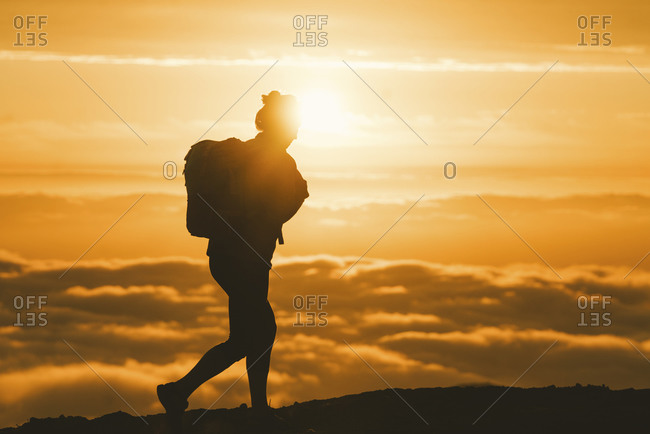 Hiker walking along the ridge of a fog enshrouded mountain peak