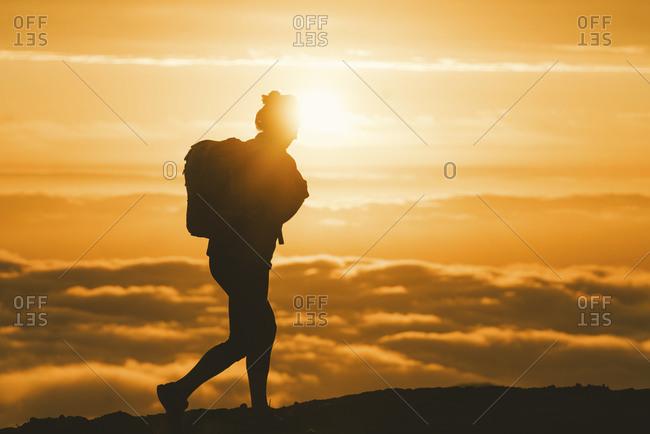 Hiker walking along the ridge of a fog enshrouded mountain peak