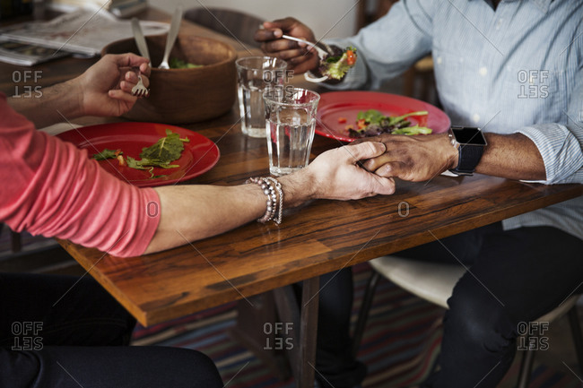 A couple holding hands at the table