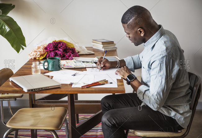 Profile of a man working on fashion sketches on a wood table