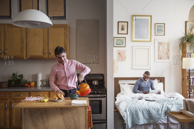 Man working in bed while his husband prepares breakfast