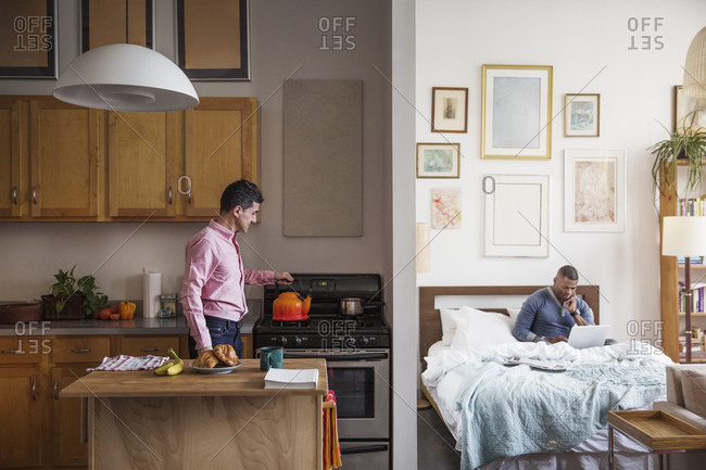 Man working in bed while his husband makes breakfast