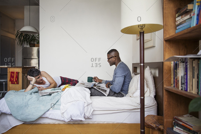 Couple reading the newspaper together in bed