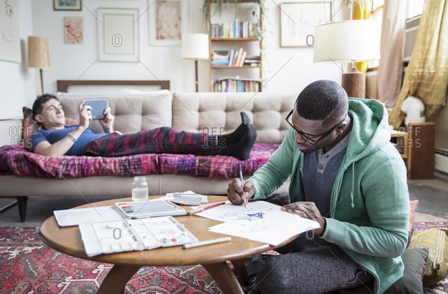 Man sketches on coffee table as his husband rest on couch with tablet
