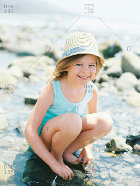 Little girl crouching in on a rocky shore smiling