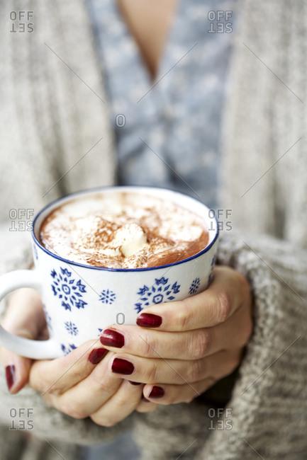 Woman hands holding mug with hot chocolate