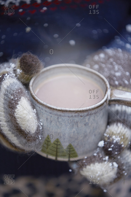 Hands in mittens holding mug with hot chocolate