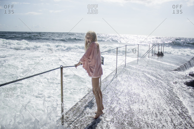 Girl standing on pier during high tide