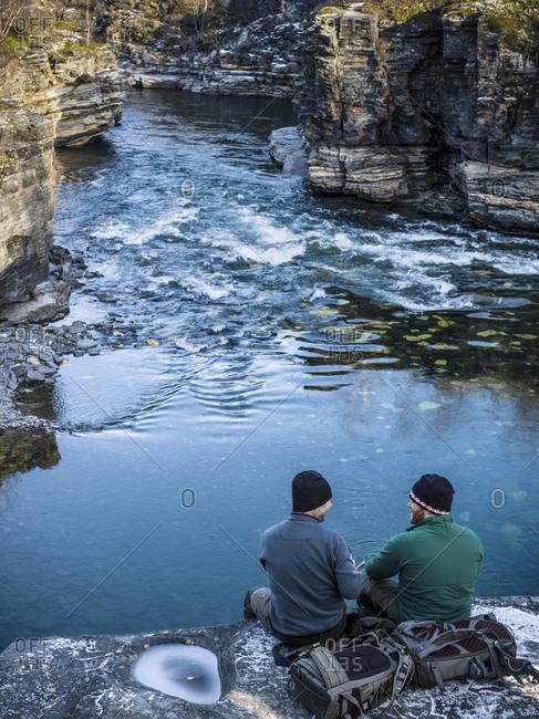 Men sitting at river