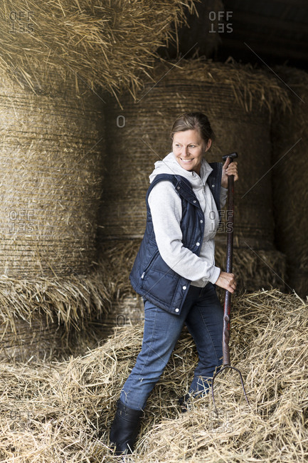 Smiling woman moving hay with pitchfork