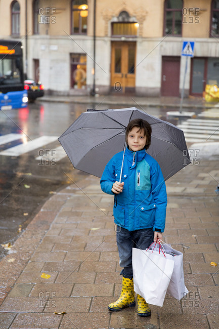 Boy at rain with paper bags
