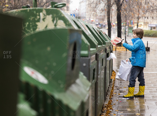 Boy putting waste into recycling bin