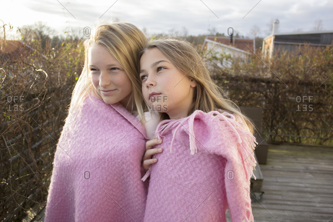 Two girls wrapped in blanket