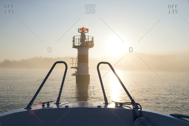Boat approaching tower on lake at sunrise