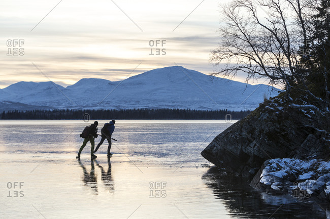 Two people skating on ice